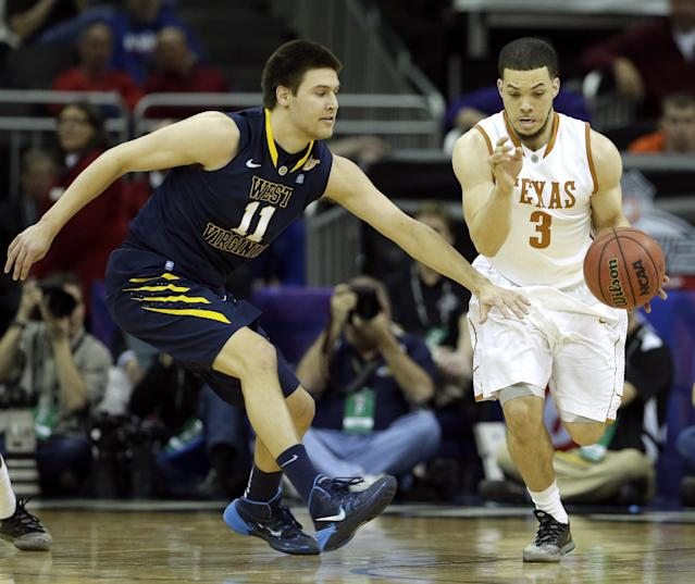 West Virginia's Nathan Adrian (11) pressures Texas' Javan Felix (3) during the first half of an NCAA college basketball game in the Big 12 men's tournament on Thursday, March 13, 2014, in Kansas City, Mo. (AP Photo/Charlie Riedel)