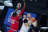 Michigan forward Austin Davis (51) shoots under Ohio State forward E.J. Liddell (32) in the first half of an NCAA college basketball game at the Big Ten Conference tournament in Indianapolis, Saturday, March 13, 2021. (AP Photo/Michael Conroy)