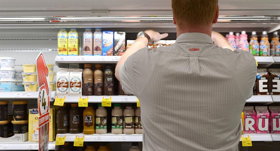 A file image of a Coles worker stacking a drinks fridge.