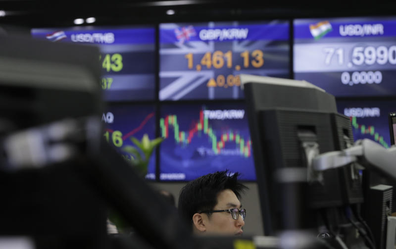 A currency trader watches computer monitors near the screens showing the foreign exchange rates at the foreign exchange dealing room in Seoul, South Korea, Tuesday, Dec. 18, 2018. Asian stocks fell on Tuesday, tracking losses on Wall Street as traders braced for an interest rate hike by Federal Reserve. (AP Photo/Lee Jin-man)