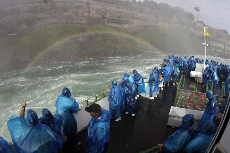 FILE - In this Aug. 31, 2011 file photo, Maid of the Mist's Senior Capt. Malcolm Bunting, not shown, pilots tourist in front of a rainbow on the Maid of the Mist tour boat in Niagara Falls, Ontario. The tour company chosen to take over the Niagara Falls tour boat business in Canada says it plans to build customized new boats and upgrade amenities while maintaining the things that have made the sightseeing rides so popular for more than 100 years. (AP Photo/David Duprey, File)