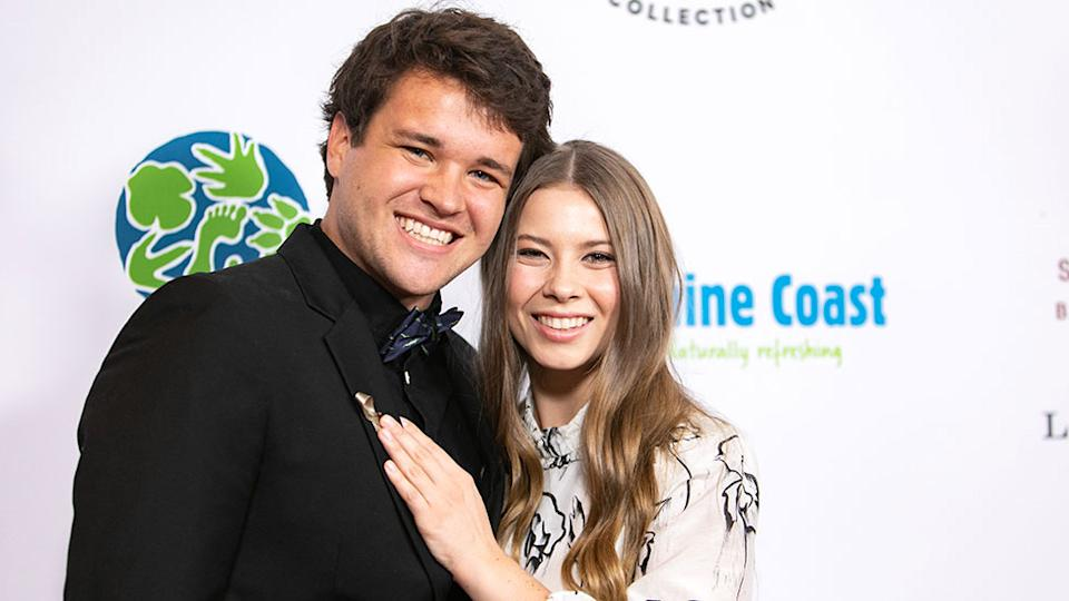 Bindi Irwin puts her hand on Chandler Powell's chest as the couple step out together on the red carpet