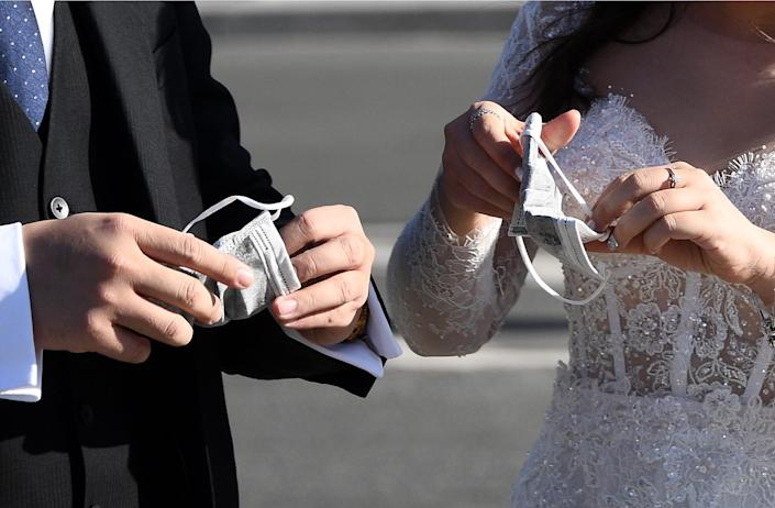 Vietnamese tourists wearing wedding clothes put on face masks in Paris on March 15, 2020 amid the COVID-19 outbreak, caused by the novel coronavirus. - France on March 14, 2020 drastically stepped up its measures against the spread of the coronavirus, announcing the closure of all non-essential public places including restaurants and cafes.