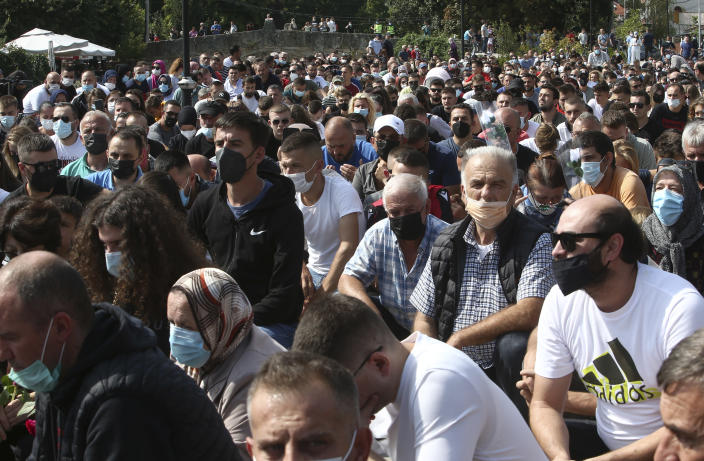 People kneel to honor the victims of the fire, near the burned out makeshift hospital, in North Macedonia's northwestern town of Tetovo, Saturday, Sept. 11, 2021. Hundreds of people have marched Saturday in northwestern town of Tetovo to honor their 14 countrymen killed in a deadly fire that broke earlier this week and destroyed COVID-19 field hospital. (AP Photo/Boris Grdanoski)