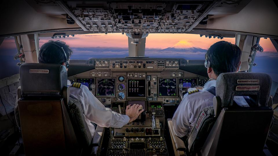 commercial airplane pilots flying at sunset