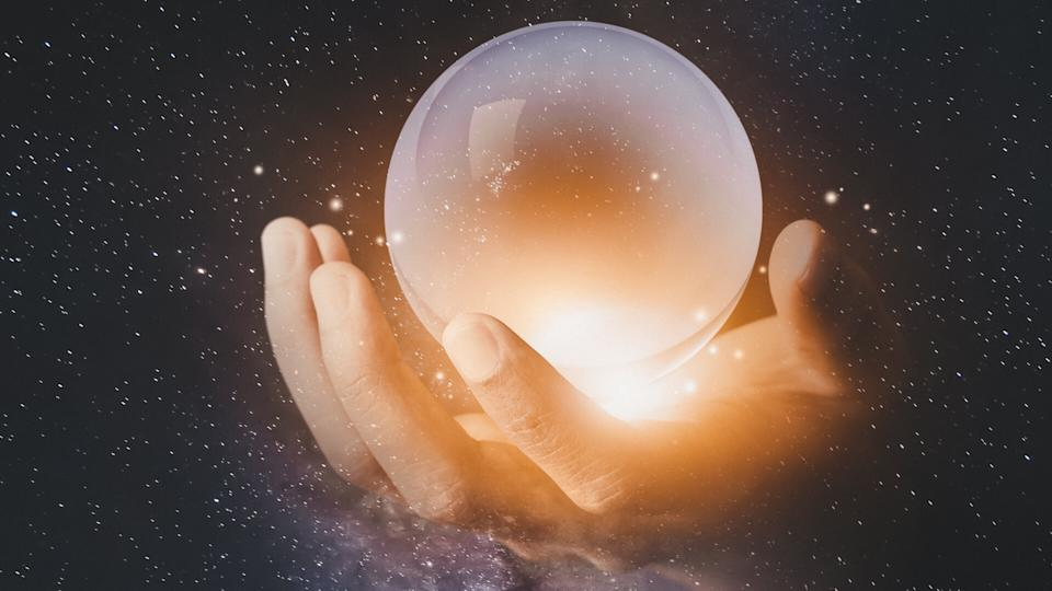 businessman hand holding crystal clear ball with galaxy universe space background.