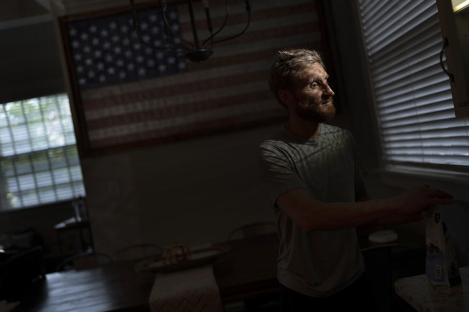 Brad Snyder prepares tea for his wife in their kitchen decorated with a flag handcrafted by Brooklyn firefighters using recycled firehose, in Princeton, N.J., on Wednesday, Aug. 4, 2021. Losing his sight, he says, seems to matter more to other people. A Navy explosives expert, Snyder stepped on hidden mine in Afghanistan in 2011 as he moved to help a group of Afghan commandos badly injured by another blast. In moments he went from thinking he was dead, to relief that he was alive, to confusion as he stood up with blood pouring from his face. (AP Photo/Emilio Morenatti)