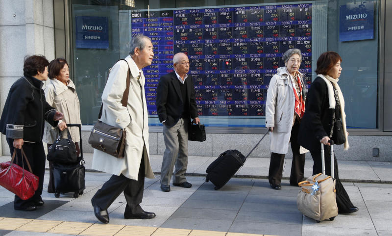 People walk by an electronic stock board of a securities firm in Tokyo Tuesday, Nov. 12, 2013. Asian stock markets mostly traded higher Tuesday after the Dow Jones industrial average hit another all-time high. Tokyo's Nikkei jumped 318.84 points, or 2.23 percent and closed at 14,588.68. (AP Photo/Koji Sasahara)