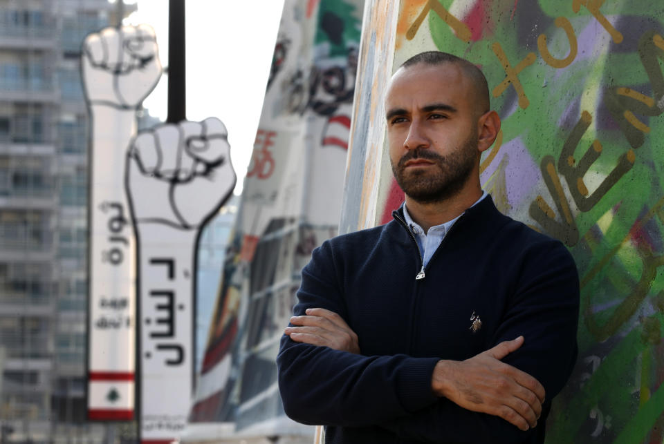 "Jad al-Rayess, a Lebanese anti-government activist, stands in front of large cardboard fist labelled: ""Revolution,"" background, in Beirut, Lebanon, Wednesday, Nov. 18, 2020. A year after anti-government protests roiled Lebanon, dozens of protesters are being tried before military courts that human rights lawyers say grossly violate due process and fail to investigate allegations of torture and abuse. (AP Photo/Hussein Malla)"