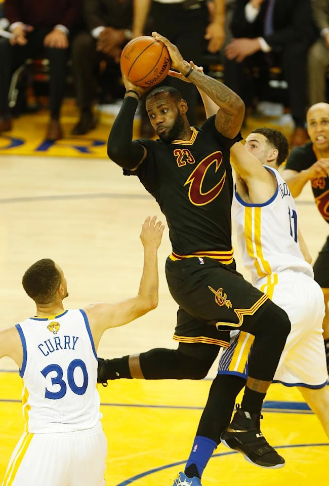 """(FILES) This file photo taken on June 18, 2016 shows Cleveland Cavaliers forward LeBron James as he looks to pass the ball over Golden State Warriors guard Stephen Curry during the second quarter in Game 7 of the NBA Finals in Oakland, California. NBA superstar LeBron James is endorsing Hillary Clinton for president of the United States in a move that could carry a lot of weight with voters in the pivotal state of Ohio. """"I support Hillary because she will build on the legacy of my good friend, President Barack Obama,"""" James wrote in an Op-Ed piece published on the Business Insider website on October 2, 2016. (AFP Photo/Beck Diefenbach)"""