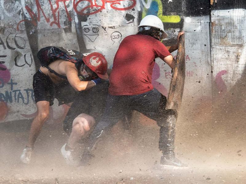 Demonstrators take cover as they clash with riot police during a protest against the government: AFP/Getty