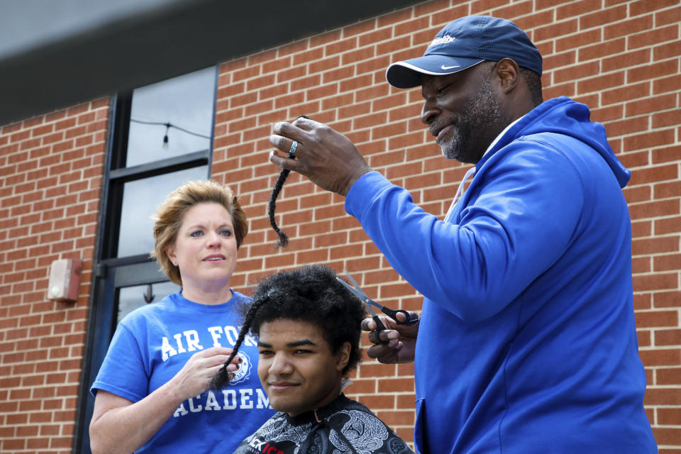 """In this photo provided by Gregg Gelmis, Kelly Moïse, left, watches her husband, Patrick Moïse, cut their son Kieran's hair during a live donation fundraiser, """"Kieran's Curls for Cancer,"""" for the nonprofit Children with Hair Loss and St. Jude Children's Research Hospital, Saturday, May 29, 2021, in Huntsville, Ala. So far, they've raised $35,000. (Courtesy of Gregg Gelmis via AP)"""