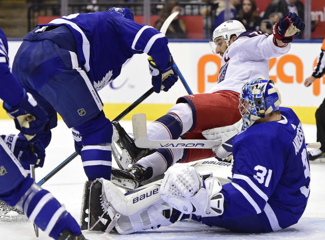 Toronto Maple Leafs defenseman Jake Muzzin (8) knocks Columbus Blue Jackets left wing Nick Foligno (71) over Maple Leafs goaltender Frederik Andersen (31) during first-period NHL hockey game action in Toronto, Monday, Oct. 21, 2019. (Frank Gunn/The Canadian Press via AP)