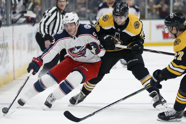 Boston Bruins' Jake DeBrusk (74) battles Columbus Blue Jackets' Matt Duchene (95) for the puck during the first period of an NHL hockey game in Boston, Saturday, March 16, 2019. (AP Photo/Michael Dwyer)