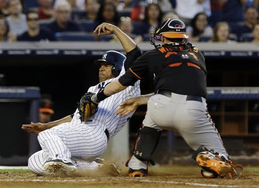 New York Yankees' Vernon Wells, left, slides past Baltimore Orioles catcher Matt Wieters to score during the fourth inning of a baseball game on Friday, July 5, 2013, in New York. (AP Photo/Frank Franklin II)