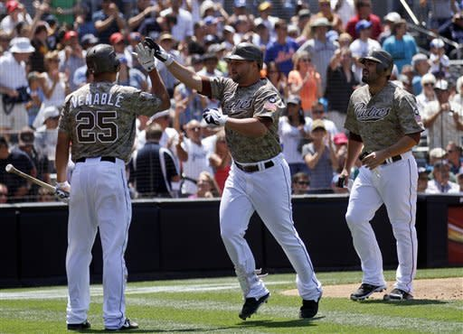 San Diego Padres' Yonder Alonso, center, is congratulated by teammate Will Venable after hitting a two-run home run against the New York Mets during the third inning of a baseball game on Sunday, Aug. 5, 2012, in San Diego. Padres' Carlos Quentin, right, also scored on Alonso's hit. (AP Photo/Lenny Ignelzi)