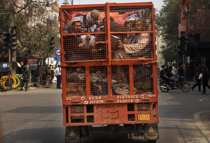 FILE - In this Wednesday, Feb. 26, 2020, file photo, a group of Muslims huddle together in the back of a mini truck and leave the area with their belongings after Tuesday's communal violence in New Delhi, India. Many of the Muslim victims of last year's bloody violence say they have run repeatedly into a refusal by police to investigate complaints against Hindu rioters. Some hope the courts will still come to their help. But others now believe the justice system under Prime Minister Narendra Modi's Hindu-nationalist government has become stacked against them. (AP Photo/Rajesh Kumar Singh, File)