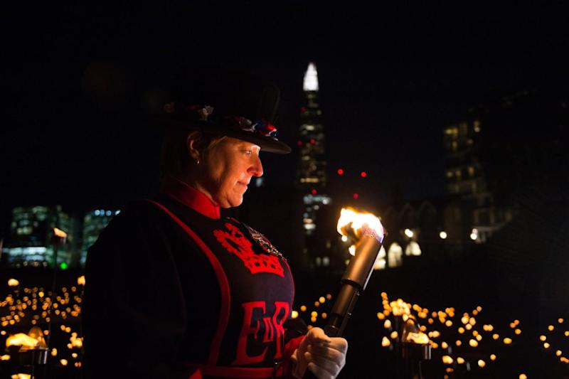 Moira Cameron Yeoman Warder of the Tower of London holds a torch during the service. (MoD)
