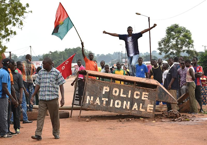 A man waves the Burkina Faso flag (L) as people protest in the city of Hounde, capital of Tuy Province, in east central Burkina Faso, on September 19, 2015 (AFP Photo/Sia Kambou)
