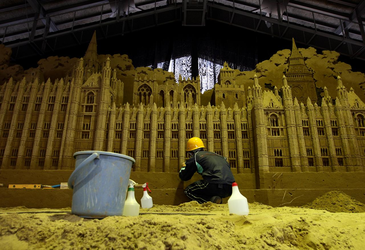 A sand sculptor finishes a sand replica titled 'Big Ben in Westminster' at Sand Museum located in the Tottori Dune on April 1, 2012 in Tottori, Japan. (Photo by Buddhika Weerasinghe/Getty Images)