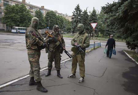 Armed pro-Russian separatists look on at a town center in Snizhnye in eastern Ukraine June 12, 2014. REUTERS/Shamil Zhumatov
