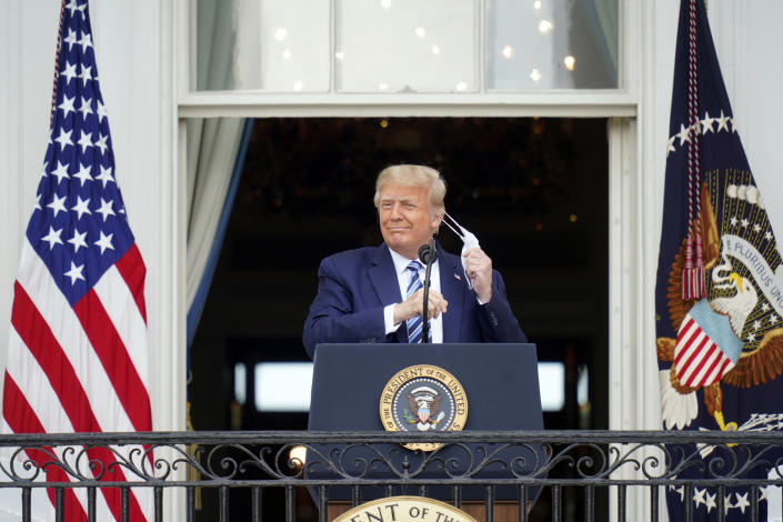 President Donald Trump takes off his face mask as he appears on the balcony during a rally at the White House in Washington, Oct. 10, 2020, his first public event since being hospitalized for COVID-19. (Doug Mills/The New York Times)