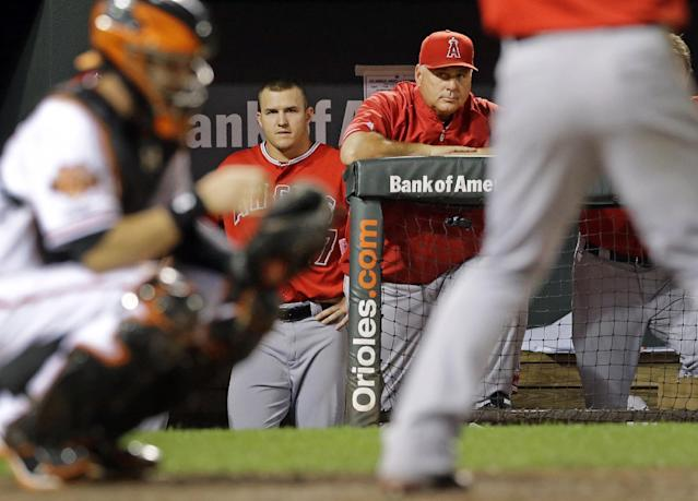Los Angeles Angels center fielder Mike Trout, back left, and manager Mike Scioscia look on from the dugout in the ninth inning of a baseball game against the Baltimore Orioles, Wednesday, July 30, 2014, in Baltimore. Baltimore won 4-3. (AP Photo/Patrick Semansky)