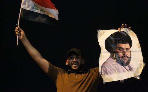 An Iraqi man celebrates with a picture of Shia cleric Moqtada al-Sadr in Baghdad - Credit: AFP
