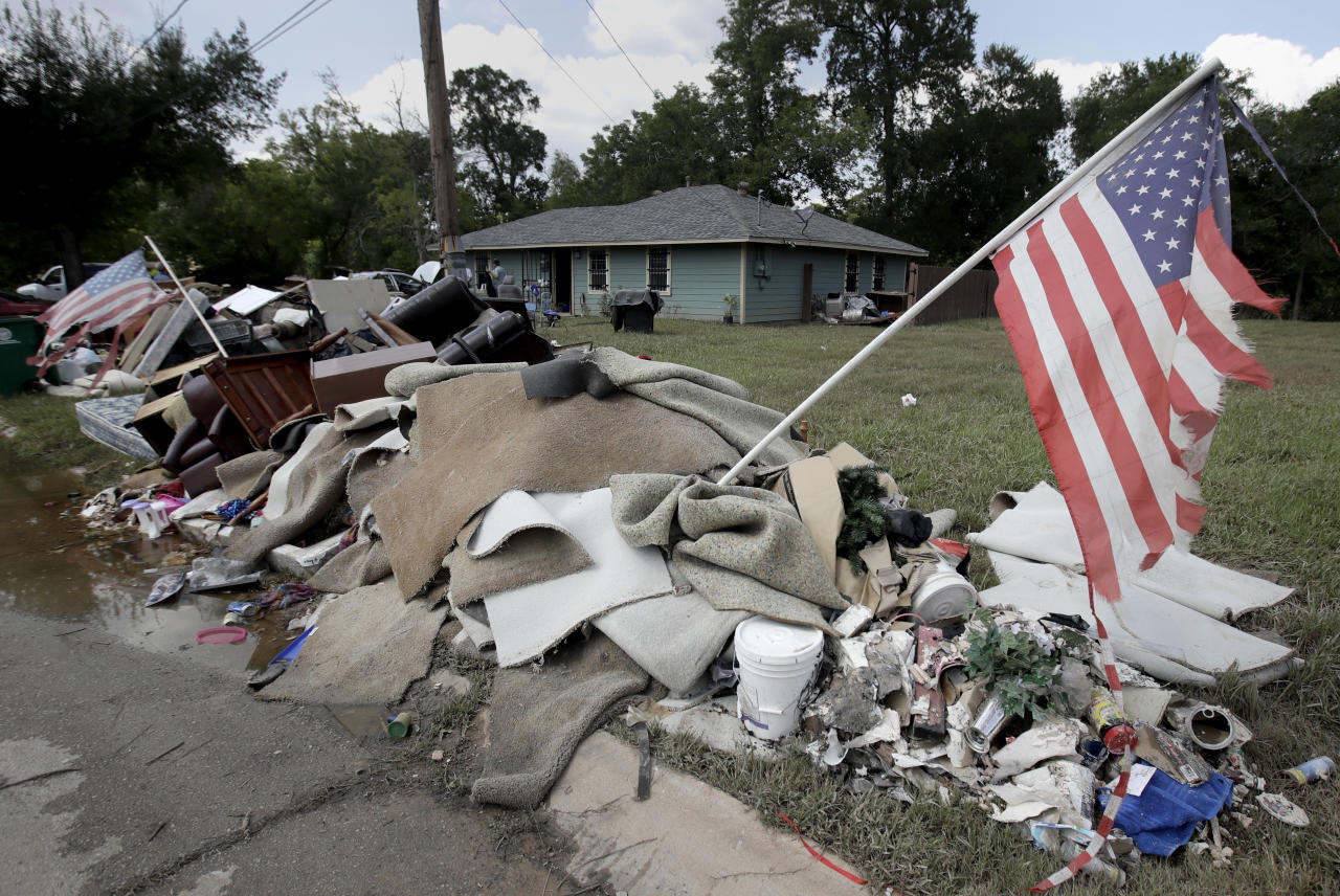 <p>Tattered flags fly over a pile of water-soaked items as people clean up in a flood ravaged neighborhood Thursday, Aug. 31, 2017, in Houston. The city continues to recover from record flooding caused by Harvey. (Photo: Charlie Riedel/AP) </p>