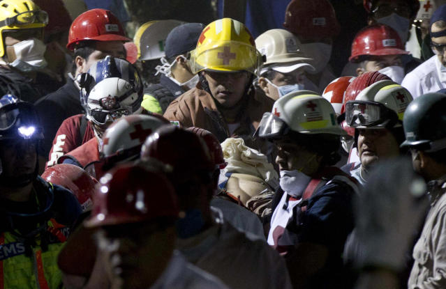 Rescue workers and firefighters carry an injured person after an explosion in a building at Mexico's state-owned oil company PEMEX complex, in Mexico City, Thursday Jan. 31, 2013. The explosion killed more than 10 people and injured some 80 as it heavily damaged three floors of the building. According to civil protection and local media some people remained trapped in the debris from the explosion, which occurred in the basement of an administrative building next to the iconic, 52-story tower of Petroleos Mexicanos, or PEMEX. (AP Photo/Eduardo Verdugo)