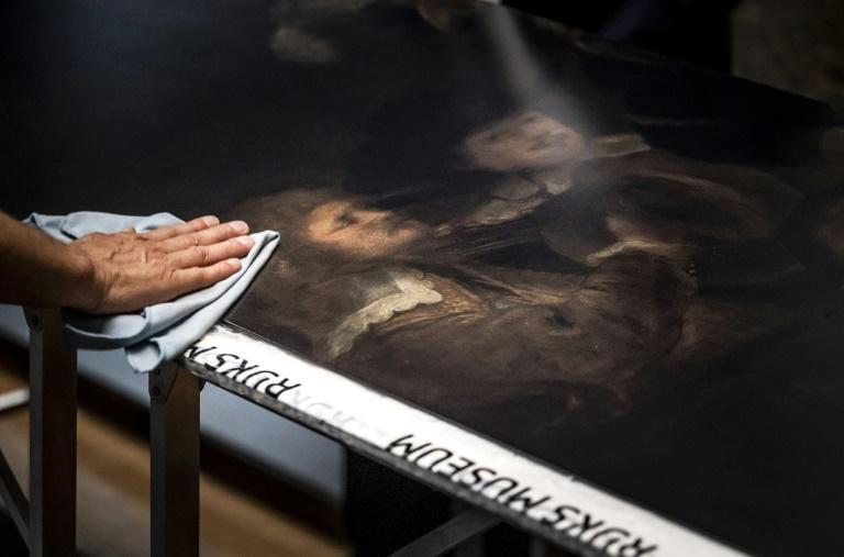 Workers clean a section of the recreation of Rembrandt's masterpiece