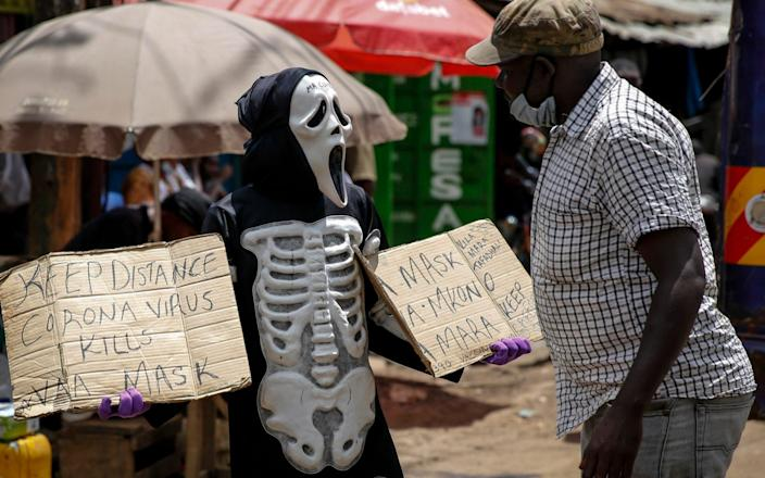 James Kiriva, who took the initiative to educate his community about the importance of taking precautions to curb the spread of the coronavirus walks around Kiberia dressed as a skeleton to spread his message in English and Swahili - AP Photo/Brian Inganga