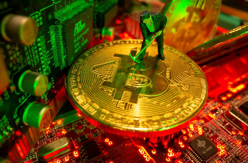 FILE PHOTO: A small toy figure and representations of the virtual currency Bitcoin stand on a motherboard in this picture illustration