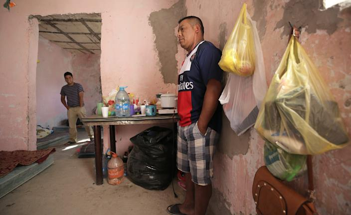 Francisco Sical, right, found shelter with his 10-year-old daughter in summer 2019 in a half-finished house in Juárez. A dozen migrants from his native Guatemala, and Honduras and El Salvador, were waiting on court hearings in the U.S. under the Trump administration's Migrant Protection Protocols.