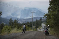 Alfred Higginbottom, of the Skuppah Indian Band, a Nlaka'pamux First Nations government, watches as a wildfire burns on the side of a mountain in Lytton, B.C., Thursday, July 1, 2021. (Darryl Dyck/The Canadian Press via AP)