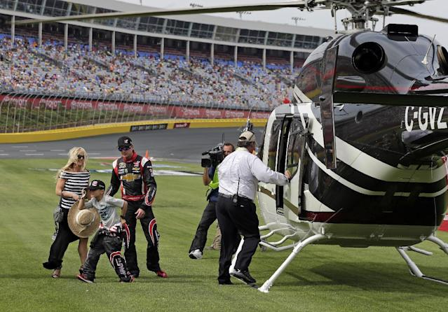 Driver Kurt Busch, right, arrives with girlfriend Patricia Driscoll, left, and her son, Houston, center, for the NASCAR Sprint Cup series Coca-Cola 600 auto race at Charlotte Motor Speedway in Concord, N.C., Sunday, May 25, 2014. Busch finished sixth in the Indianapolis 500 race earlier. (AP Photo/Chuck Burton)