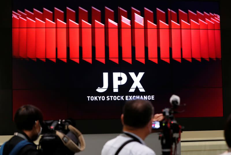 TV camera men wait for the opening of market in front of a large screen showing stock prices at the Tokyo Stock Exchange in Tokyo