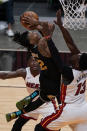 Memphis Grizzlies guard Ja Morant (12) drives to the basket as Miami Heat center Bam Adebayo (13) defends, during the second half of an NBA basketball game, Tuesday, April 6, 2021, in Miami. (AP Photo/Marta Lavandier)