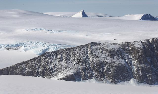 <p>A nanatuk (center), or mountain peak, projects through ice in a view from NASA's Operation IceBridge research aircraft, near the coast of the Antarctic Peninsula region on Oct. 31, 2017, above Antarctica. (Photo: Mario Tama/Getty Images) </p>