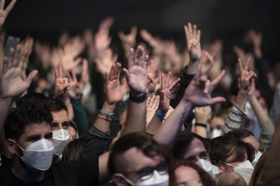 People attend a music concert in Barcelona, Spain, Saturday, March 27, 2021. Five thousand music lovers are set to attend a rock concert in Barcelona on Saturday after passing a same-day COVID-19 screening to test its effectiveness in preventing outbreaks of the virus at large cultural events. The show by Spanish rock group Love of Lesbian has the special permission of Spanish health authorities. While the rest of the country is limited to gatherings of no more than four people in closed spaces, the concertgoers will be able to mix freely while wearing face masks. (AP Photo/Emilio Morenatti)