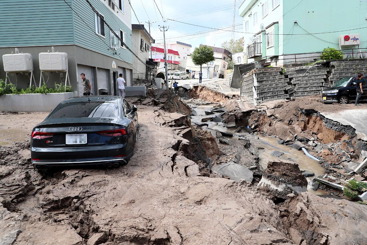 <p>A car is seen stuck on a road damaged by an earthquake in Sapporo, Hokkaido prefecture on September 6, 2018. (Photo: JiJi Press/AFP/Getty Images) </p>