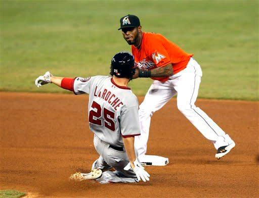 Washington Nationals' Adam LaRoche (25) breaks up the double play by coming in high against Miami Marlins' Jose Reyes (7) during a baseball game at Marlins Park in Miami, on Monday, May 28, 2012. (AP Photo/Joel Auerbach)