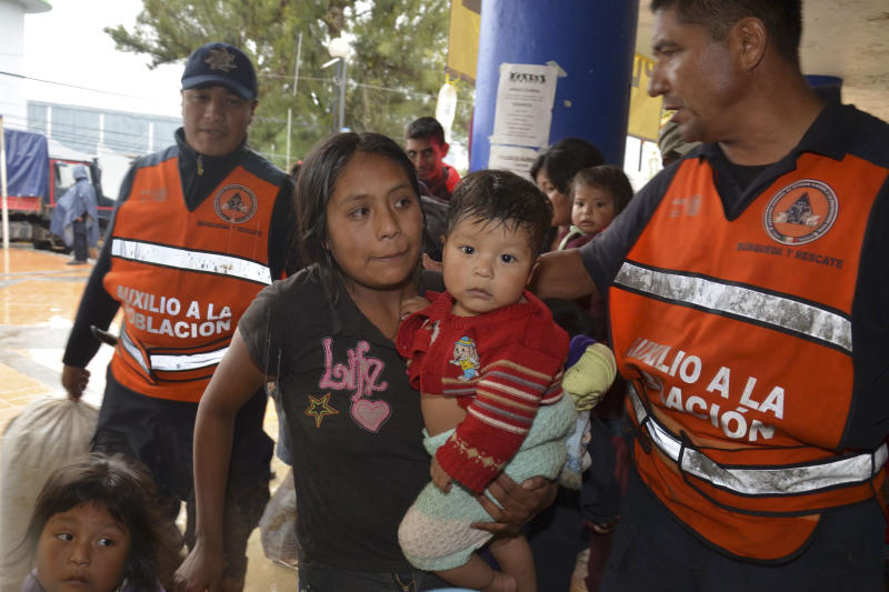 A woman and her children arrive at a makeshift shelter in the city of Chilpancingo, Mexico, Monday Oct. 21, 2013. At least 120 families from nearby communities were evacuated when Hurricane Raymond gained more strength and threatened to hurl heavy rains onto a sodden region already devastated by last month's Tropical Storm Manuel. (AP Photo/Alejandrino Gonzalez)