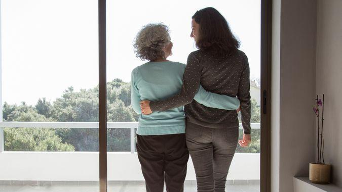 Rear view of happy mother and daughter standing embracing at window.