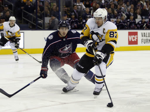 Pittsburgh Penguins forward Sidney Crosby, right, controls the puck against Columbus Blue Jackets defenseman Zach Werenski during the first period of an NHL hockey game in Columbus, Ohio, Saturday, March 9, 2019. (AP Photo/Paul Vernon)