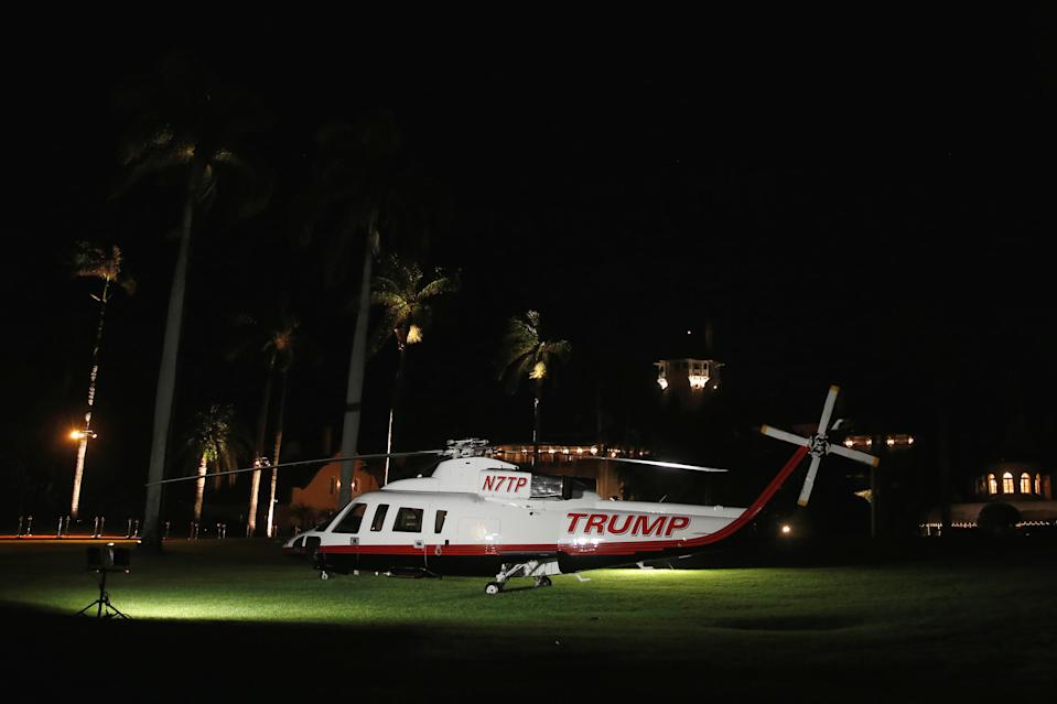 A Trump-branded helicopter sits on the lawn to greet guests as they arrive for a New Year's Eve party at Mar-a-lago in 2016. (Jonathan Ernst/Reuters)