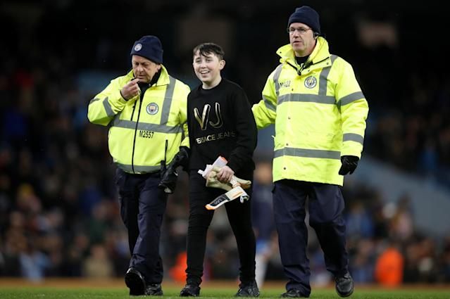 Soccer Football - International Friendly - Italy vs Argentina - Etihad Stadium, Manchester, Britain - March 23, 2018 Stewards escort a fan off the pitch after he is given Argentina's Willy Caballero's match gloves Action Images via Reuters/Carl Recine