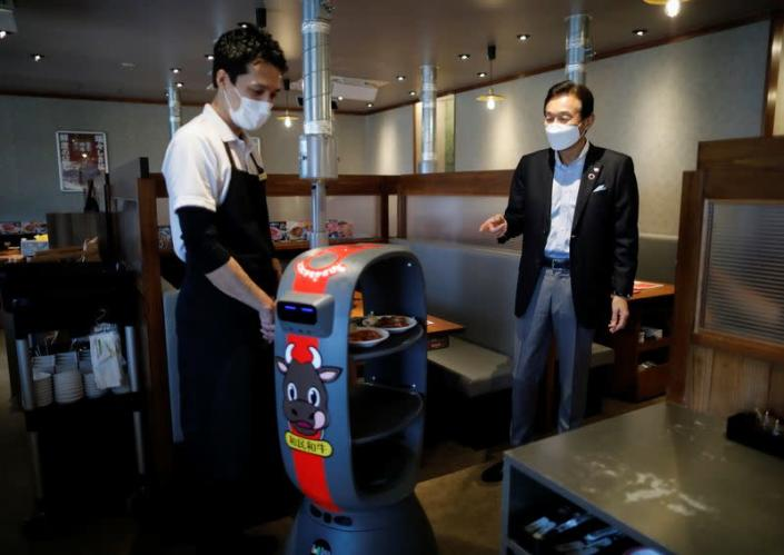 Miki Watanabe, Chairman and CEO of Watami Co. talks with a staff member next to a serving robot at their yakiniku barbecue restaurant named 'Yakiniku no Watami', in Tokyo