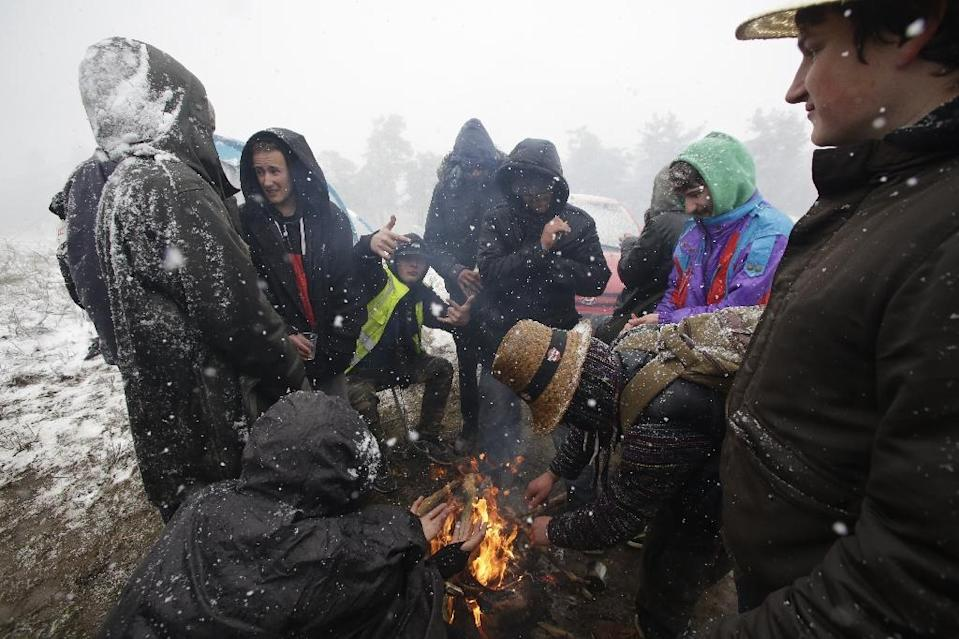 Participants at the Teknival music festival in Feniers, central France, were caught off guard by a spring snowstorm on Saturday, May 4 (AFP Photo/PASCAL LACHENAUD)