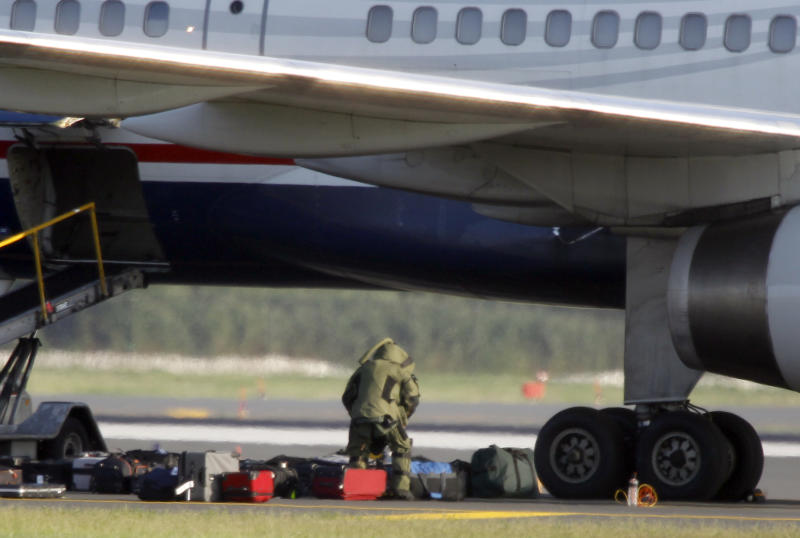 A explosives disposal expert wearing a protective suit examines a piece of luggage near a US Airways plane on the tarmac at Philadelphia International Airport Friday, Aug. 5, 2011 in Philadelphia. Passengers aboard a US Airways flight that flew in from Scotland were removed and the plane taken to another part of Philadelphia International Airport because of an unspecified threat on Friday.  (AP Photo/Alex Brandon)